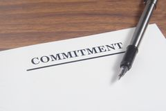 Commitment Letter. And pen at wooden board Royalty Free Stock Photo