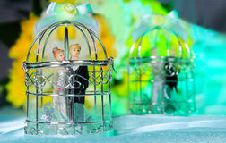 Commitment of love and marriage concept. Photo of wedding couple figurines in a beautiful cage as symbol for commitment and long lasting marriage royalty free stock image