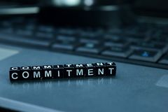 Commitment text wooden blocks in laptop background. Business and technology concept royalty free stock image