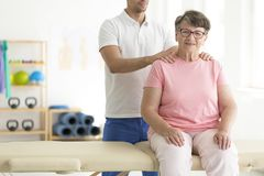 Elderly lady on physiotherapy. Committed elderly lady being rehabilitated by a physiotherapist on physiotherapy royalty free stock image
