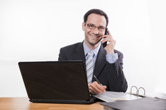 Committed employee with glasses smiling at phone Royalty Free Stock Photography