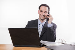 Committed employee smiling at phone Royalty Free Stock Photo