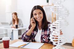 Committed excited woman calling someone while studying Stock Photo