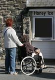 Committed Helper. Elderly female in a wheelchair being pushed by a female carer stock photos