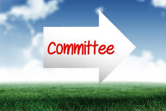 Committee against blue sky over green field. The word committee and arrow against blue sky over green field Royalty Free Stock Images