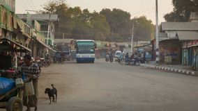 Common Asian Burmese dusty road with transport traffic on a street with cars water carriage cart and Royalty Free Stock Photos