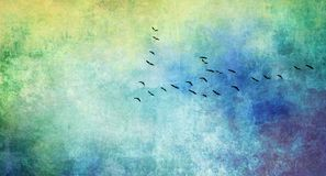 Birds in flight formation on textured background. Common cranes in flight formation at passage of birds. Watercolor texture in blue and ocher shades added Stock Photo
