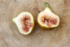 Common fig fruits cut open showing the flesh on wooden background, Top view. royalty free stock images