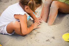 Common fun in the sand. Two little girls playing in sand together. Close up royalty free stock photography