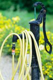 Common home garden hose. Coiled up and hanging on a fountain royalty free stock images