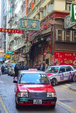 Common red taxi in Hong Kong driving through Sheung Wan area Royalty Free Stock Photo