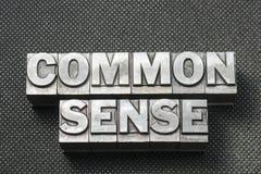 Common sense bm. Common sense phrase made from metallic letterpress blocks on black perforated surface royalty free stock photo