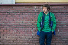 Common young man wearing green t-shirt jacket and jeans against a red brick wall looking sideways. Young man wearing a shirt and jeans against a brick wall Stock Photography