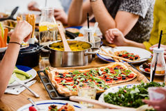 Communal table with fresh pizza. Millet groats healthy salad and hummus on veggie dinner Royalty Free Stock Images
