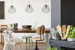 Communal table and pendant lamps. Room with communal table, chairs, pendant lamps, kitchen cart Stock Images