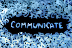 Communicate. Word COMMUNICATE made of small glowing letters, black background Stock Images