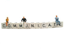 Communicate. Couple of people sitting on the word communicate stock photography
