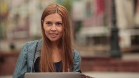 She communicates in social networks and the smiles on the street with a laptop. stock footage