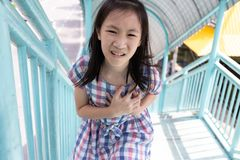 Communicates the symptoms of heart disease,immediately,Asian girl on the pedestrian overpass royalty free stock photography