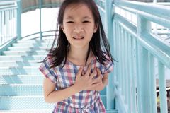 Communicates the symptoms of heart disease,immediately,Asian girl on the pedestrian overpass stock image