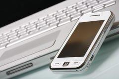 Communicateur blanc sur l'ordinateur portatif argenté. Images stock