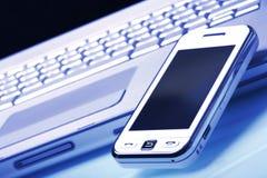 Communicateur blanc sur l'ordinateur portatif argenté. Teinte bleue. Images libres de droits