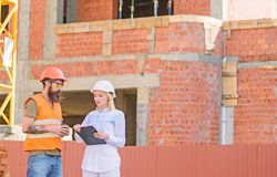 Communicatie van het bouwteam concept Bespreek vooruitgangsplan De de vrouweningenieur en bouwer delen bouwwerf mee stock foto