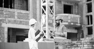 Communicatie van het bouwteam concept De vrouweningenieur en de brutale bouwer delen bouwwerfachtergrond mee royalty-vrije stock afbeelding