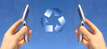 Communicating. A pair of hands hold up identical mobile phones into the sky with the phones open. A recycling symbol is between the open phones Stock Photography