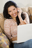 Communicating Latin Beauty. A stunningly beautiful young Hispanic woman sitting on a settee having fun on her laptop and chatting on her cell phone Royalty Free Stock Image
