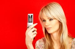 Communication. Lovely blond with phone over red background Royalty Free Stock Photography