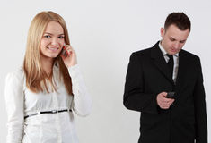Communication. Young couple using mobile phones.Selective focus on the blonde woman Stock Image