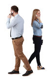 Communication. A men and a women using mobile phones passing by themselves, against a white background Stock Image