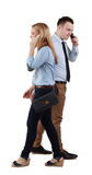 Communication. A men and a women using mobile phones passing by themselves, against a white background Stock Images