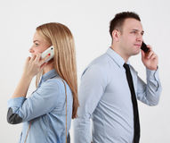 Communication. Profile of a men and a women using mobile phones passing by themselves. Selective focus on the woman Royalty Free Stock Photo