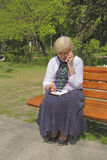 Communication. Woman calling by mobile phone and taking notice in a notebook in a park Stock Photos