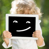 Communication. Child holding tablet PC with smile. Communication concept Stock Photography