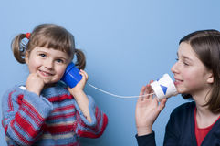 Communication. Two sisters palying with mug phone stock photography