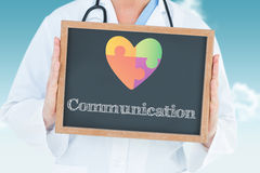 Communication against blue sky. The word communication and doctor showing chalkboard against blue sky Royalty Free Stock Image