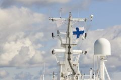 Communication antennas and finnish flag on a cruise vessel. Marine Royalty Free Stock Image
