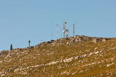 Communication antennas on a rocky hill. Stock Photography