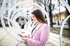 Communication avec des amis Vue de côté de la jeune femme réfléchie dans la veste rose dactylographiant quelque chose au téléphon Image libre de droits