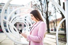 Communication avec des amis Vue de côté de la jeune femme réfléchie dans la veste rose dactylographiant quelque chose au téléphon Photographie stock libre de droits