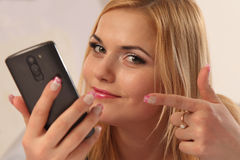 Communication. Beautiful woman pointing finger on smartphone Stock Images