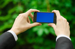 Communication and Business Subject: Hand in a black suit holding a modern phone with blue screen in the background of green grass Royalty Free Stock Photo