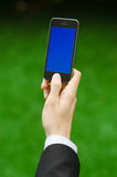 Communication and Business Subject: Hand in a black suit holding a modern phone with blue screen in the background of green grass Royalty Free Stock Images