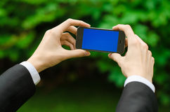 Communication and Business Subject: Hand in a black suit holding a modern phone with blue screen in the background of green grass Stock Photo