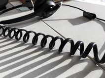 Communication Call Center Desktop Background Close-up Detail. Communication call center technology background image with headset and spiral cord closeup in Royalty Free Stock Images