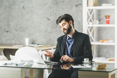 Communication concept. Smiling young man looking at laptop screen in modern office with various items on glass desk. Concrete wall background. Communication Royalty Free Stock Photo