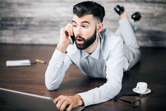 Communication concept. Surprised caucasian businessman lying on wooden floor with coffee cup, talking on phone and using laptop. Communication concept Stock Photography